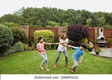 Two children are playing in the garden in summer with their mother. They are both holding one of her arms and are swinging around.