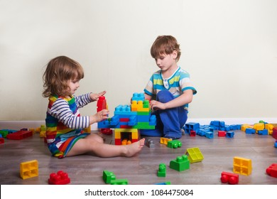 Two children  playing with lots of colorful plastic blocks constructor sitting on a floor indoor.