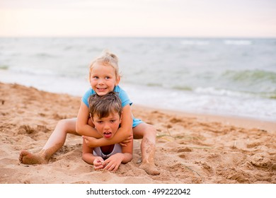 two children playing on beach with sand
