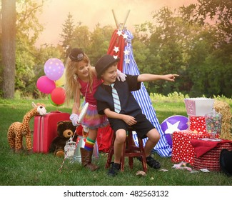 Two children are playing outside dressing up as carnival people at a circus party for an imagination or creativity concept