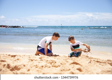 Two children playing with the sand at the beach, Kauai, Hawaii