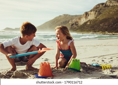 Two children playing with sand on the beach. Small boy and girl building a sandcastle on seaside on summer vacation.