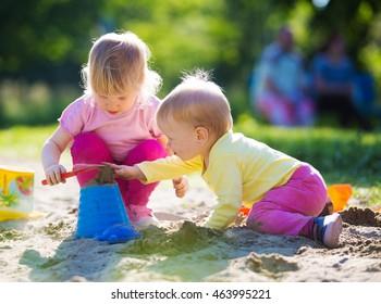 Two children playing in sandbox