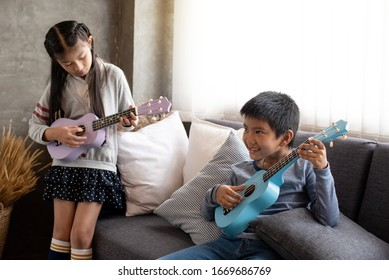 Two children playing ukulele together,with happy feeling,at home studio,beside window,blurry light around