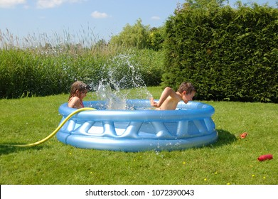 Two children playing with water in an inflatable pool in the garden.