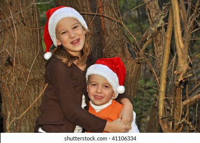 two children pose by a tree wearing santa hats