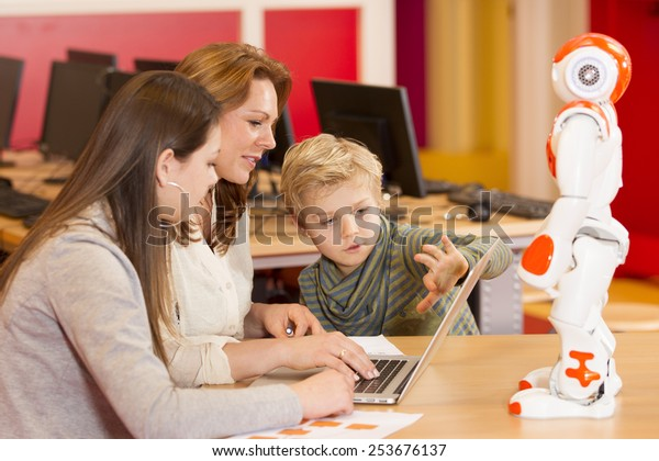Two children programming a robot with their science teacher on a primary school