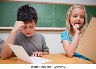 Two children reading in a classroom