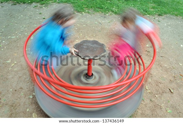 Two children in a red carousel spinning round