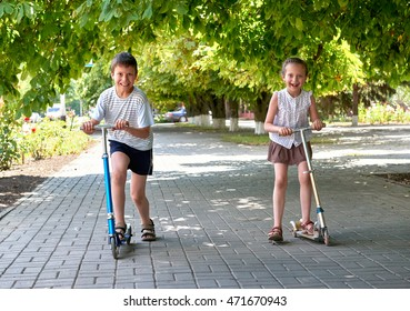 two children ride on scooters on street sidewalk in city outdoor, bright sunny day