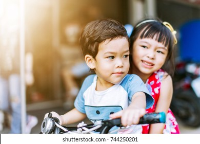 Two children riding a bicycle at home