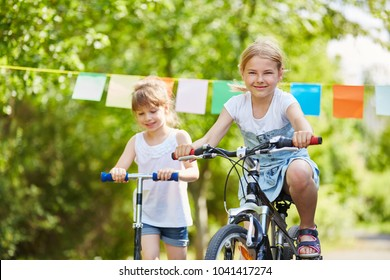 Two children riding bycicle and scooter in summer in the park