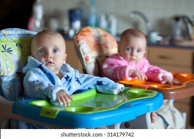 Two children in robes in high chair