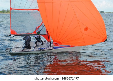 Two children sailing a racing dinghy with a large fully deployed orange coloured spinnaker for fun and in competition. Practised teamwork by junior sailors. Lake Macquarie. Photo for commercial use.