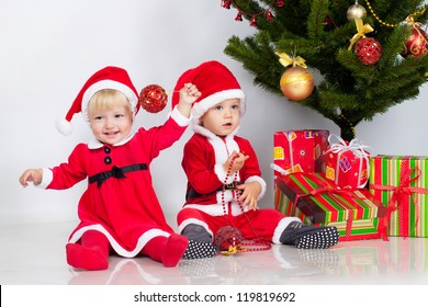 Two children sifting under christmas pine