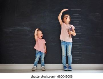 Two children sisters play together. Kid measures the growth on the background of blackboard. Concept of education.