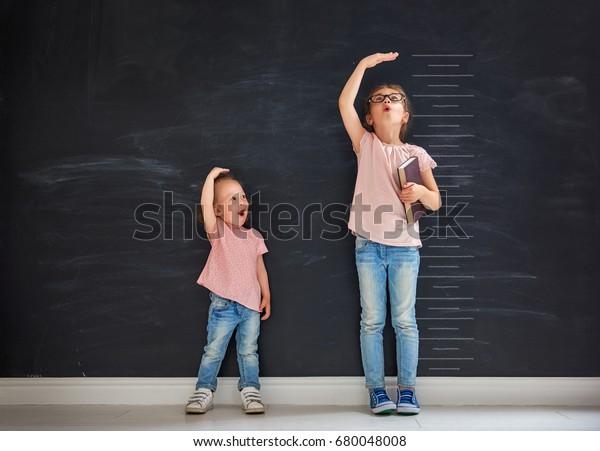 Dos hermanas infantiles juegan juntas. El niño mide el crecimiento en el fondo de la pizarra. Concepto de educación.