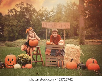 Two children are sitting outside at a wooden stand selling Halloween pumpkins for a holiday activity concept or business idea.