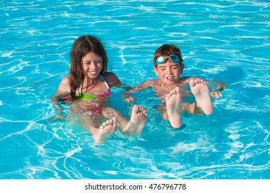 Two children sitting in water with their feet out