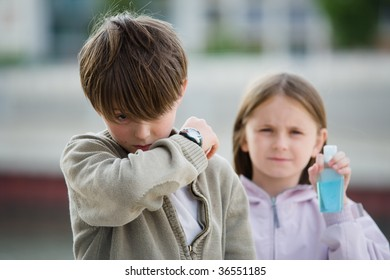 Two children stand in an urban setting, one sneezing into their elbow, the other holding a bottle of hand cleanser.