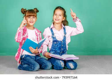 Two children study a school lecture. The concept of childhood, learning, friendship, family, school, lifestyle.