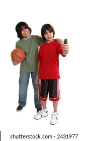 Two children taking a cell phone picture of themselves playing basketball