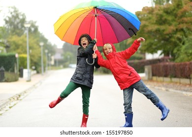 Two children, teenager twin brothers having fun outside jumping on the street under rain sharing together colorful umbrella
