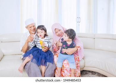 Zwei Kinder und ihre Großeltern spielen mit Seifenblasen, während sie zusammen auf der Couch im Wohnzimmer sitzen. Schuss zu Hause