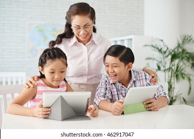 Two children and their teacher reading information on tablet computer