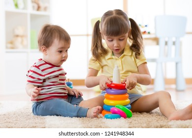 Two children together. The big sister helps the younger brother to assemble the toy pyramid