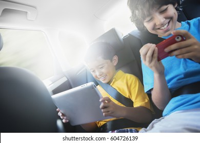 Two children travelling in the back seat of a car, one using a digital tablet and one a handheld game,