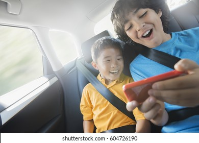 Two children travelling in the back seat of a car sharing a handheld games tablet,