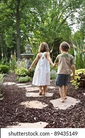 Two children walking down a garden path to a fountain