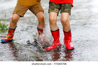Two children wearing red rain boots jumping into a puddle. Close up. Kids having fun with splashing with water. Happy children during heavy summer shower rain