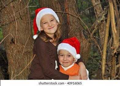 two children wearing santa hats embrace by a tree