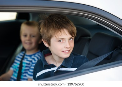 Two children wearing seatbelts in the car in a close up shot