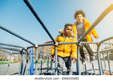 Two children with yellow coats jumping on elastic bed in a playground in a sunny day
