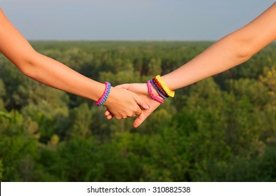 two children's hands with bracelets
