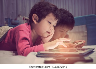 two chinese children addicted tablet. asian child watching tablet, kid use telephone together on their bed, play phone, kid addict smartphone