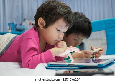 two chinese children addicted tablet, asian child watching tablet, kid use telephone together on their bed, play phone, kid addict smartphone