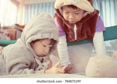 two  chinese children addicted tablet. asian child watching tablet  / kid use telephone together on their bed