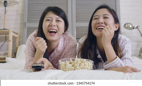 two chinese girls in nightwear watching movies with popcorn lying in bed. happy women laughing cheerfully holding remote control switch tv program to comedy funny video. relax enjoyment junk food