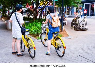 Two Chinese Women Ride Shared Bikes by OfO Company, at Popular Commercial Street Called Huangxinglu, Changsha City, Hunan Province, China, July, 2017. China Bike-Sharing Scene.
