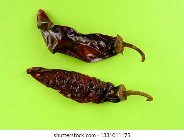 Two Chipotle Peppers (dried jalapeño, Capsicum annuum, Morita Variety), isolated on a violet background