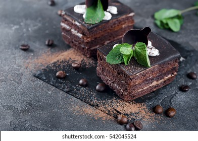 Two chocolate cakes with peppermint and coffee beans on a dark background concrete