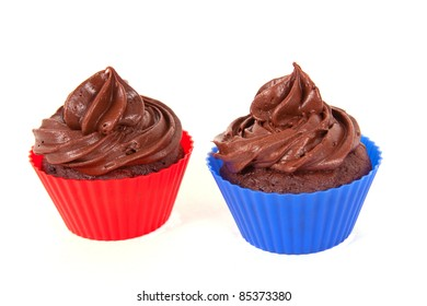 Two chocolate cupcakes in red and blue holders