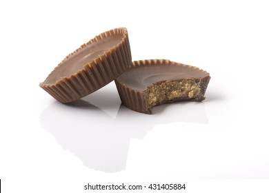 Two chocolate peanut butter cups, one with a bite taken out of it, on white with reflection and shadows.