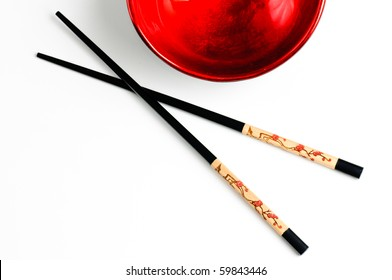 Two chopsticks next to a black and red bowl