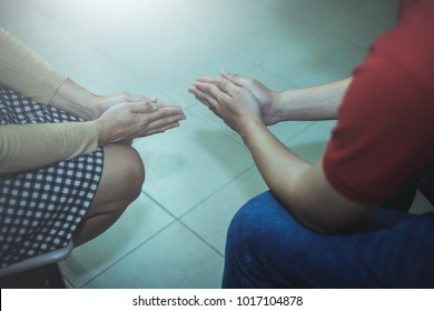 Two christian people sitting on chair and pray to God together, Christian background