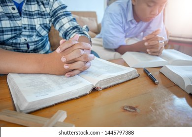 Two christian praying to God in morning on wooden table with bible.